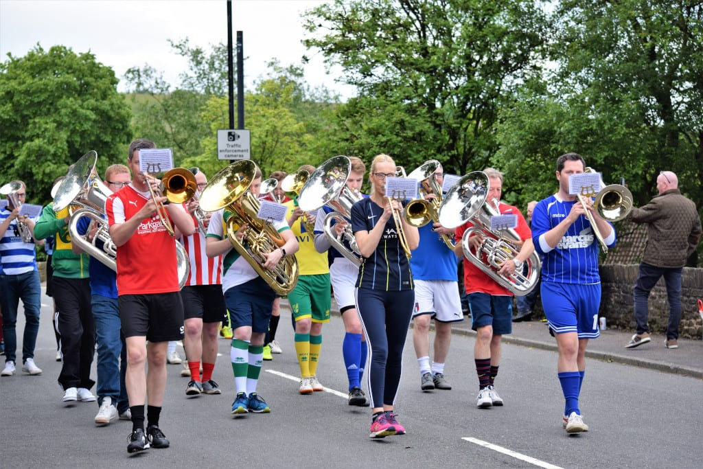 Kitted out in footbal shirts, the March of the Day Band play theThe Match of the Day theme tune as they parade through Denshaw