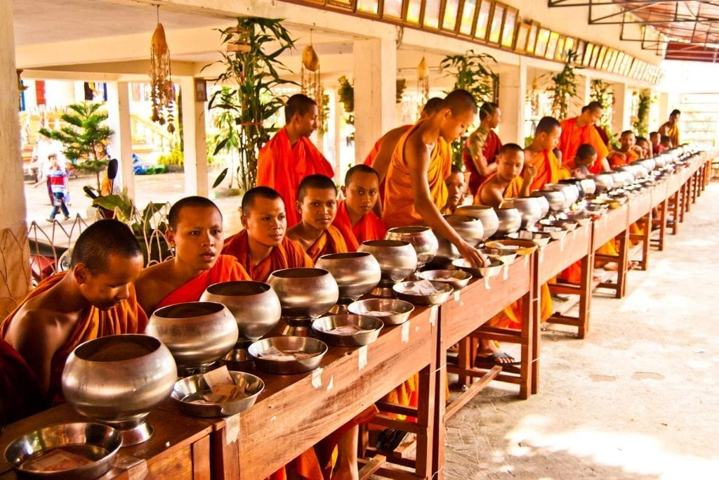 Buddhist monks at Pchum Ben await offerings of food and money