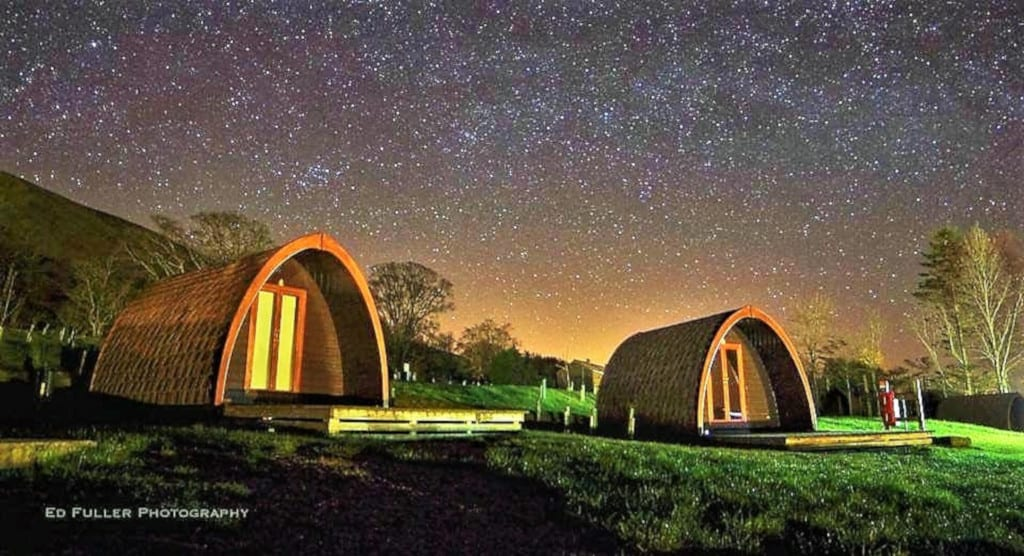 Camping pods at night at the Quiet Site