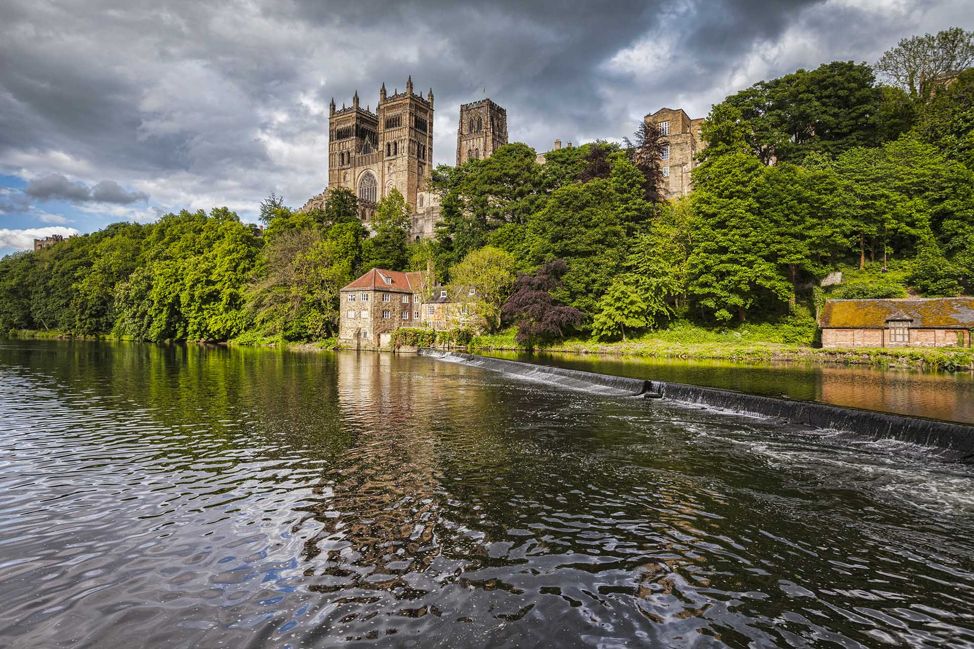 Durham Cathedral and the River Wear under a dramatic stormy sky.
