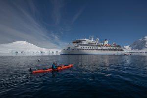 Kayaker In Front of the Greg Mortimer, Antarctica; Scott Portelli